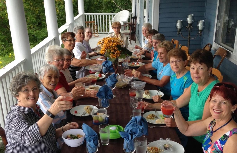 Group meal on the front porch of the Lumber Baron's House / Repas de groupe sur le balcon avant de la Maison des barons forestiers